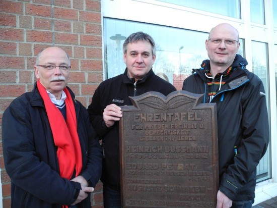 Die Ratsherren Martin Weinberg, Martin Püschel und Detlef Seiler halten die mehr als 50 Jahre alte Ehrentafel der SPD auf der auf die drei Opfer des Naziregimes hingewiesen wird.