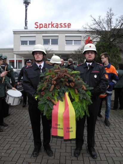 Aufstellung vor der Sparkasse mit dem Kranz und der Feuerwehr