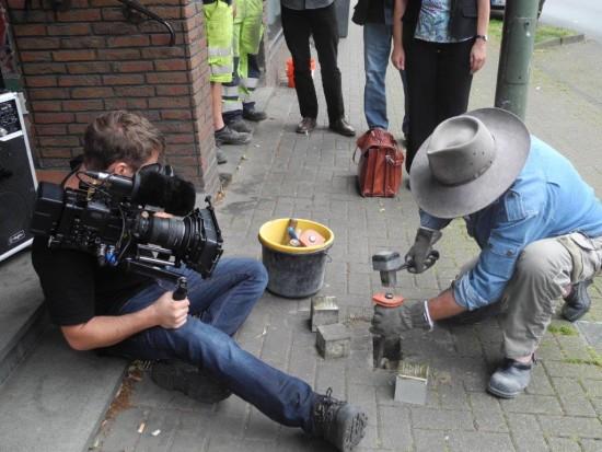 Der Künstler Gunter Demnig wird bei seiner Arbeit gefilmt